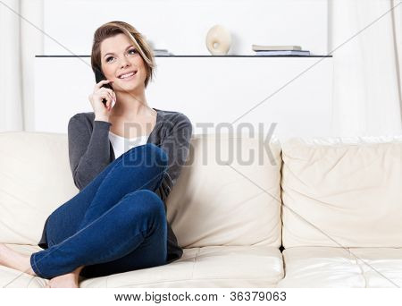 Sitting on the sofa pretty woman speaks on the phone