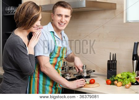 Man in striped apron slices vegetables for dinner for his girlfriend