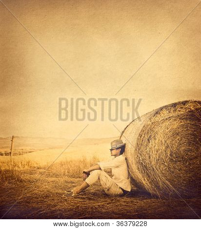 Young man relaxing against a bale of hay in vintage colors