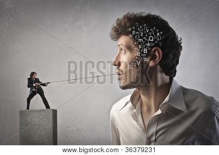 Small businessman pulling a rope and trying to pull out some alphabet letters from another man's mouth