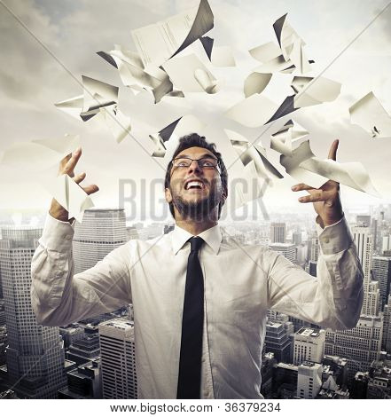 Happy young businessman throwing paper sheets in the air with cityscape in the background