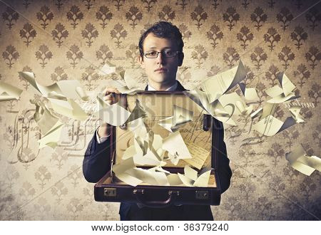 Young businessman holding an open briefcase with paper sheets flying away from it