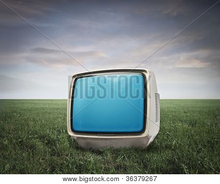 Television on a green meadow