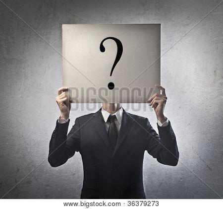 Jovem empresário, segurando um cartaz em branco com um ponto de interrogação sobre ele