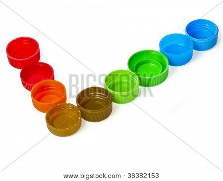 Check mark tick of color plastic bottle caps isolated on white