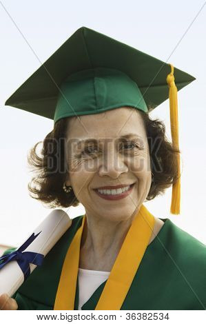 Portrait of a happy senior woman in graduation robe holding degree