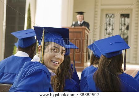Portrait of young male graduate with friends attending graduation ceremony