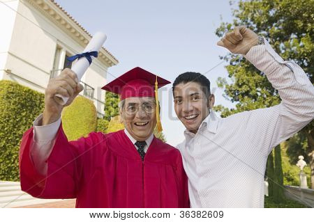 Portrait of an excited senior male graduate with son holding degree
