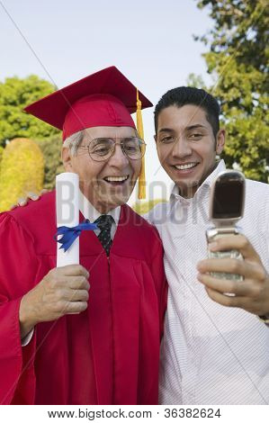 Excited senior male graduate with son taking self-portrait through cell phone