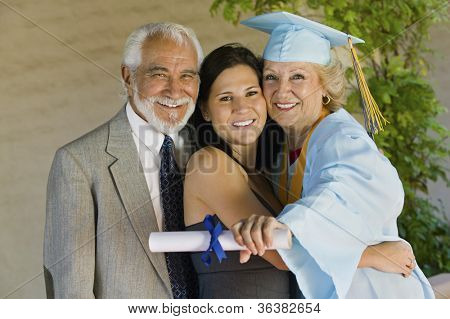 Portrait of a happy senior female graduate embracing family