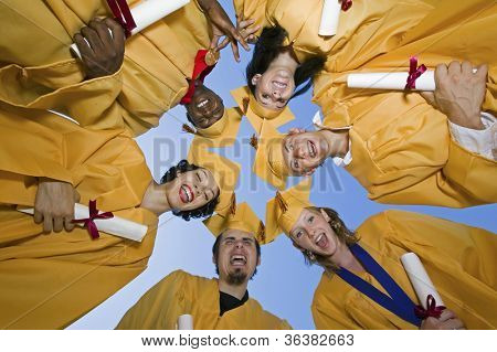 Group of multiethnic graduates with certificates forming huddle against sky