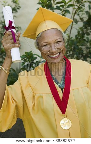 Happy senior woman with degree and medal in graduation gown
