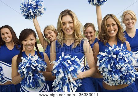 Group portrait of young cheerleaders holding pom-poms on field