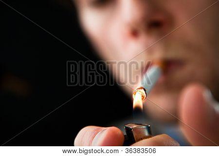 Man lighting a cigarette against a black background