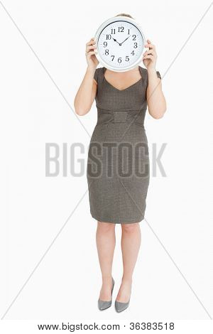 Woman holding a clock hiding her head against white background