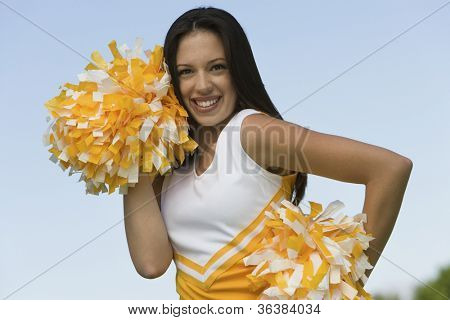 Portrait of a young beautiful cheerleader holding pom-poms
