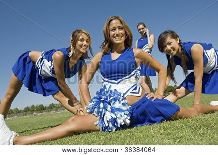 Happy young cheerleaders performing on field