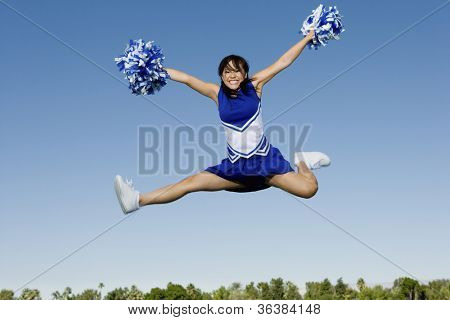 Full length of an excited young cheerleader jumping with pom-poms against sky