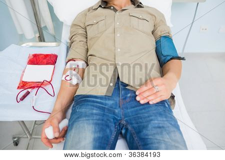 Male patient receiving a blood transfusion in hospital ward