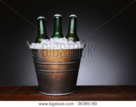 An ice bucket with three green beer bottles on a wet wood surface. Horizontal format with a light to dark gray background.