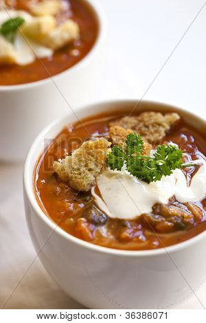 Cups of tomato soup with croutons, yogurt and parsley.