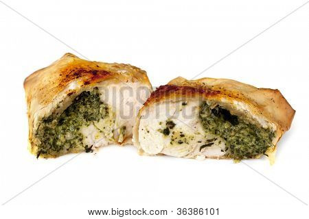 Chicken and spinach filo parcel cut in half, isolated on white background.