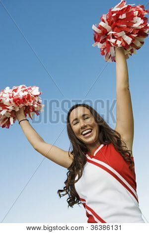 Portrait of a young cheerleader holding pom-pom against clear sky