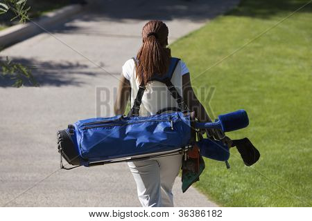 Rear view of an African American woman carrying golf bag
