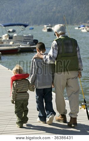 Rear view of grandfather walking with his grandsons on pier