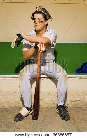 Baseball player sitting in dugout after playing a match
