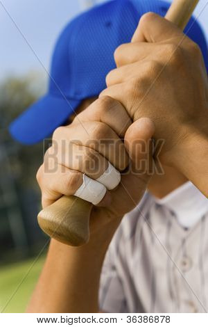 Baseball player's hand with taped fingers holding bat