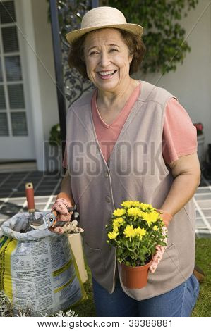 Portrait of happy senior woman holding pruner and flower pot in garden