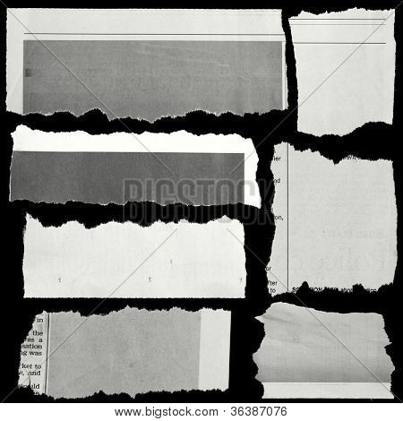 Pieces of torn paper on black. Copy space