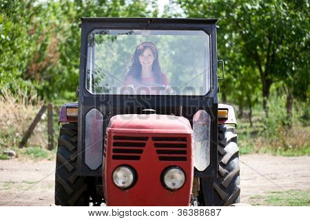 Young cute woman driving tractor