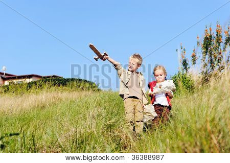 Brother and sister children playing pretend adventure game outdoors having fun in the field