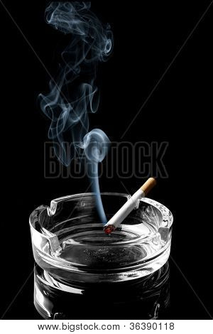Closeup of cigarette on ashtray with wisp of smoke