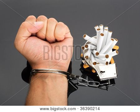 Addict hand locked to cigarettes by handcuffs