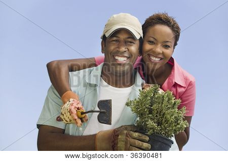 Portrait of a happy African American couple gardening against clear sky