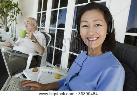 Happy mature woman listening music on laptop with senior man in background