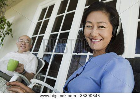Glücklich Reife Frau Musik hören am Laptop mit Alter Mann im Hintergrund