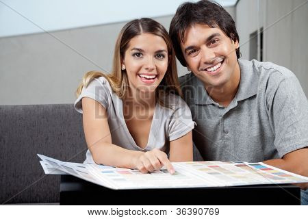 Portrait of happy young couple choosing paint colors from swatch chart