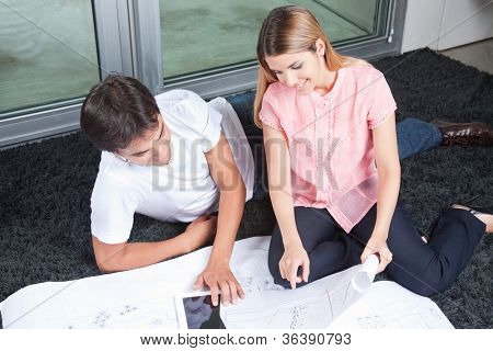 Young couple using digital tablet with blueprints .