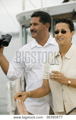 Couple on yacht with man holding binoculars and woman having coffee