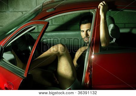 Portrait of a sexy young man sitting in red car