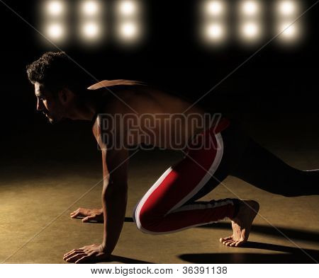 Portrait of an athlete in position to run with stadium lights in background