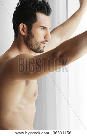Porträt eines durchdachten schön nackt jungen Mannes Blick aus einem Fenster denken