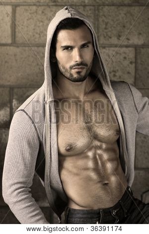 Young handsome macho man with open jacket revealing muscular chest and abs