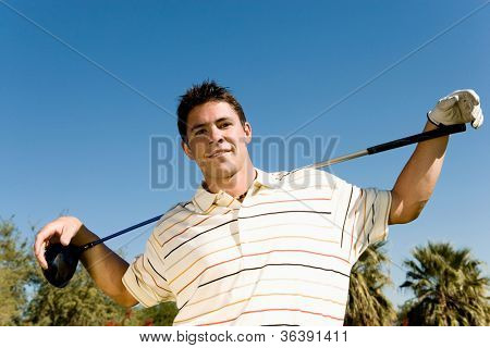 Portrait of a confident young man with golf club against clear sky
