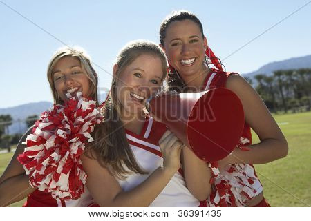 Portrait of happy cheerleader holding megaphone with friends