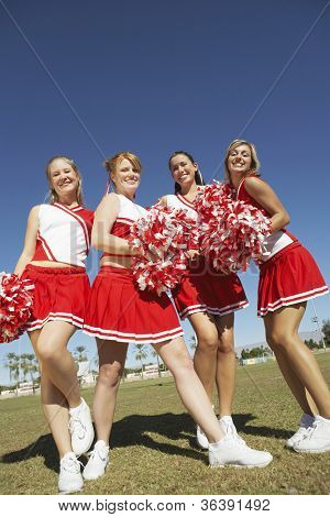 Low angle view of happy cheerleaders standing together on field